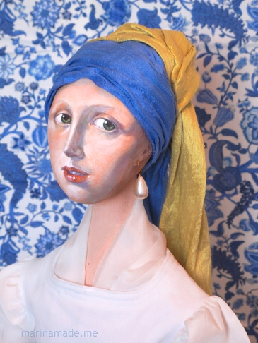 Girl Pearl Earring muse against blue Danube fabric. Made by Marina Elphick. Marina creates soft sculpted muses of the women in popular artists' lives and gives us an alternative narrative to their story. Marina's muses aim to educate and inform, appealing aesthetically to art lovers and students.