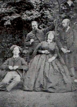 Photograph of Algernon Swinburne, Dante Gabriel Rossetti, Fanny Cornforth, and William Michael Rossetti, in the garden at Cheyne Walk.